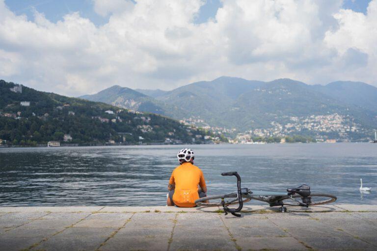 Ein Mann mit Gravelbike sitzt an einer Seepromenade