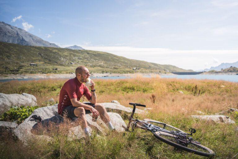 Ein Mann mit Gravelbike sitzt auf einem Stein und isst - Chris Gollhofer Fotografie
