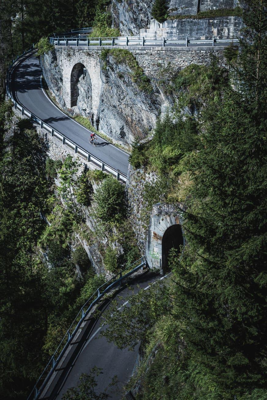 Ein Gravelbike Fahrer fährt den Splügenpass hinunter - Chris Gollhofer Sport Fotografie Italien