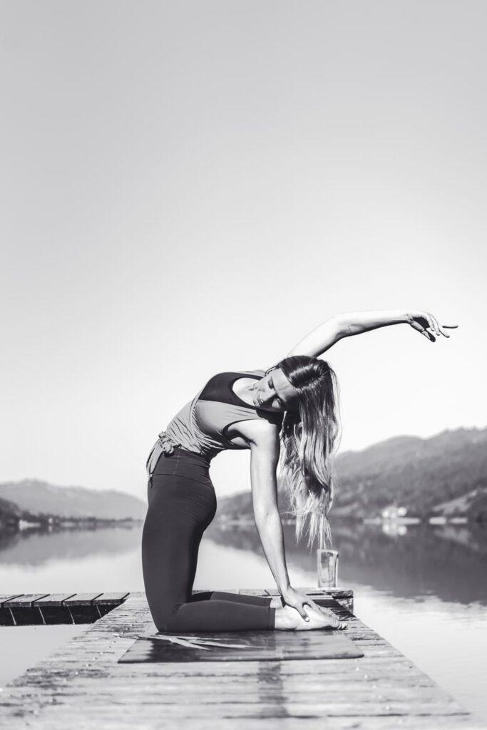 Eine Frau kniet auf einer Yogamatte auf einem Steeg - Chris Gollhofer Allgäu Sport und Lifestyle Fotograf