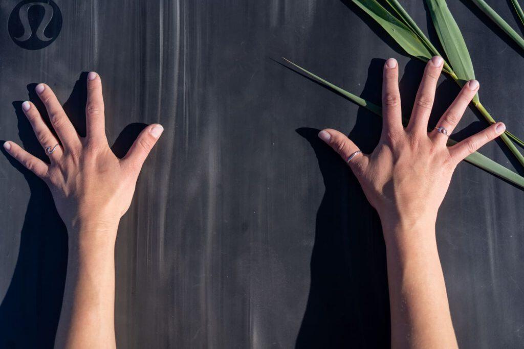 Detailaufnahme zweier Hände auf einer Yogamatte.