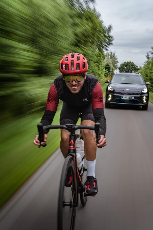 Rennradfahrer fährt vor einem Auto her