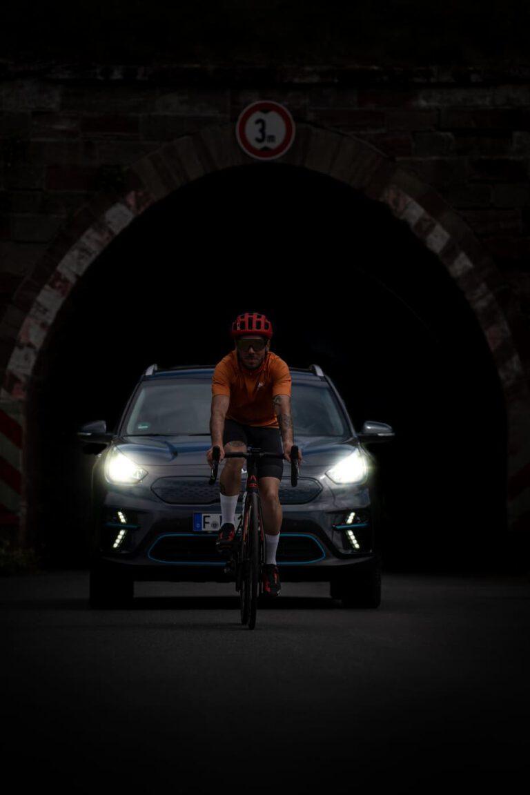 Radfahrer fährt vor einem Auto aus einem Tunnel - Chris Gollhofer Sport Fotografie