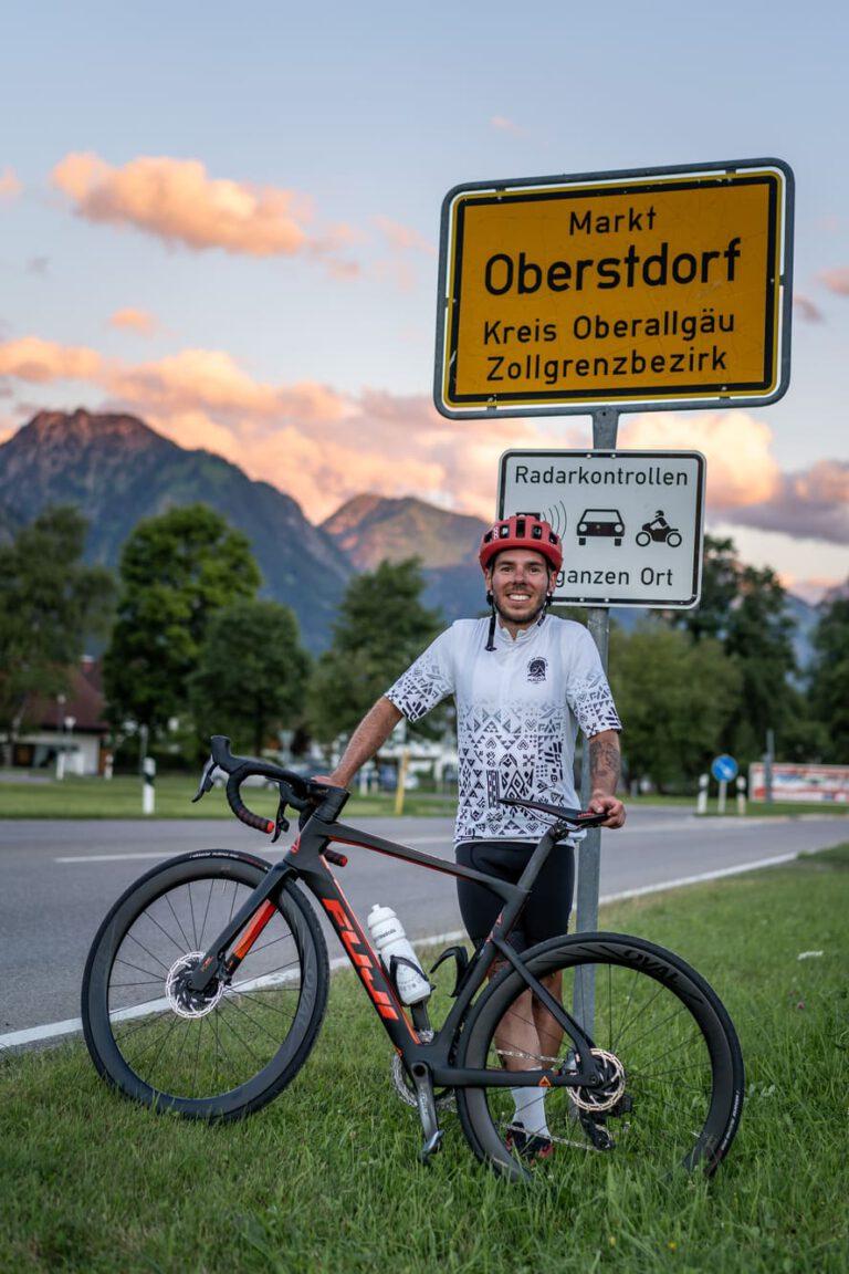 Mann mit Rennrad vor Ortsschild