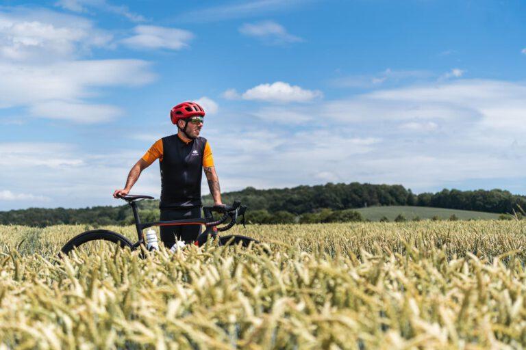 Mann mit Rennrad in einem Getreidefeld