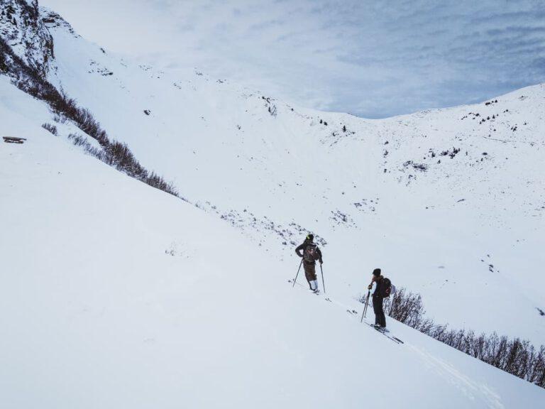 Drohnenaufnahme von zwei Personen die eine Skitour gehen