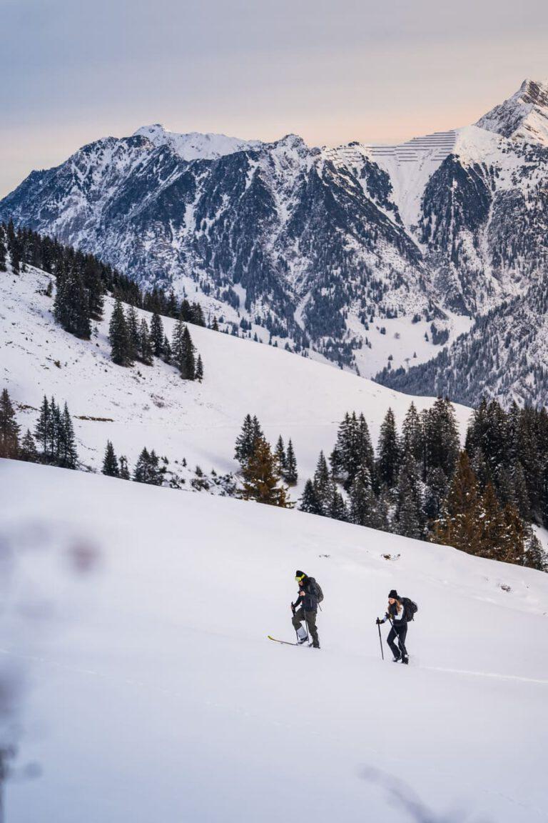 Ein Paar geht früh morgens eine Skitour