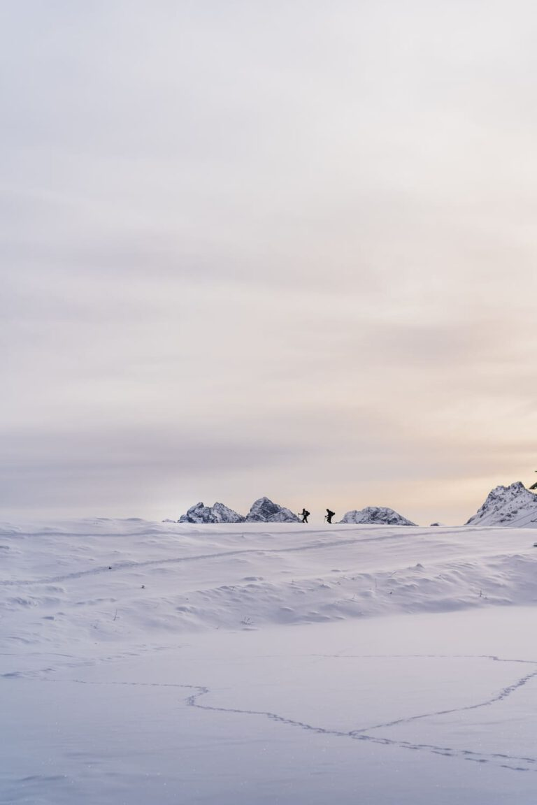 Die Silhouetten zweier Personen die eine Skitour gehen - Chris Gollhofer Lifestyle Fotografie