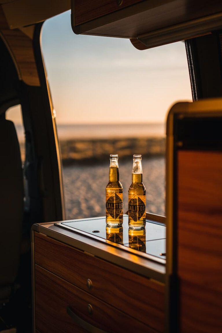 Zwei Bier auf der Küchenzeile in einem Wohnmobil am Strand - Vanlife Chris Gollhofer Fotografie