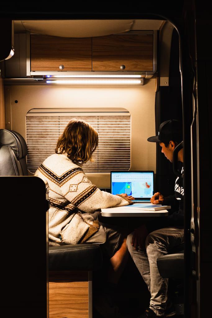 Zwei Männer schauen sich den Surfforecast auf einem Laptop man - Vanlife Surftrip Chris Gollhofer Fotografie
