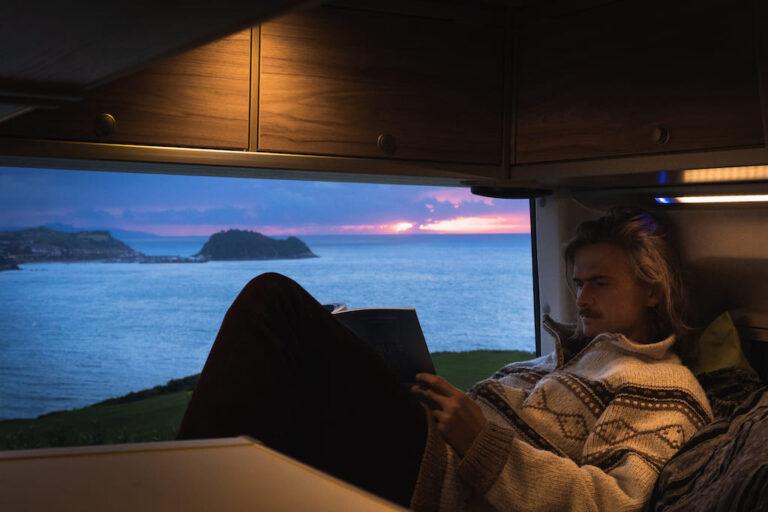 Ein Mann liest ein Buch im Wohnmobil Vanlife Surftrip Chris Gollhofer Fotografie