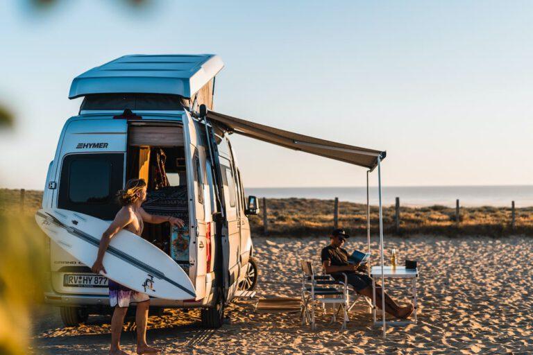 Zwei Männer an ihrem Wohnmobil am Strand bei Sonnenuntergang Vanlife Surftrip Chris Gollhofer Fotografie