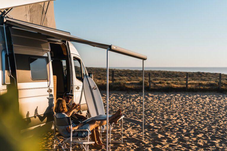 Zwei Freunde trinken ein Bier vor ihrem Wohnmobil am Strand - Vanlife Surftrip Chris Gollhofer Fotografie