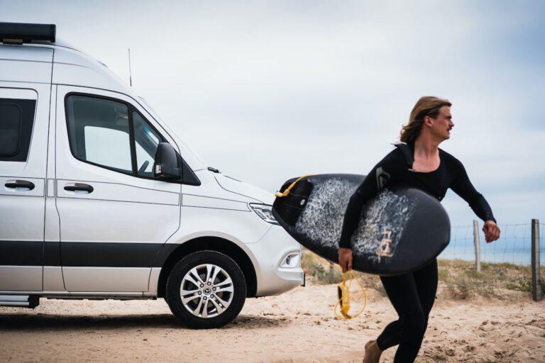 Ein Surfer läuft mit dem Surfboard unter dem Arm von einem Wohnmobil weg - Vanlife Surftrip Chris Gollhofer Fotografie