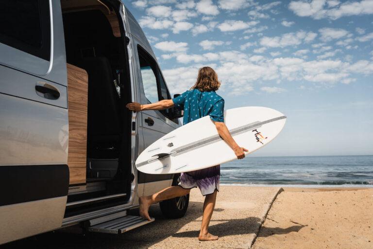 Ein Surfer steht mit Surfboard neben Wohnmobil und schaut auf das Meer - Vanlife Surftrip Chris Gollhofer Fotografie