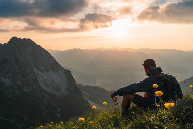 Ein Mann trinkt eiskalte Limonade auf einem Berg