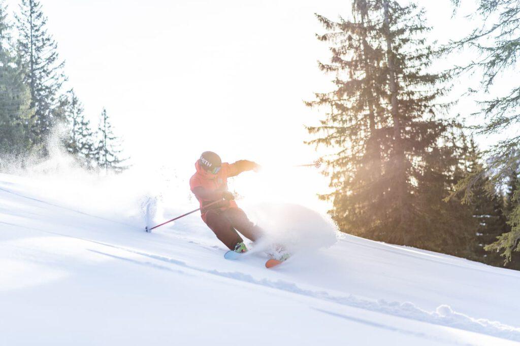 Ein Mann fährt mit Ski eine Kurve im Tiefschnee