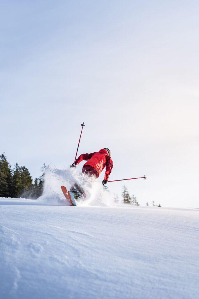 Mann fährt rückwärts im Tiefschnee Ski