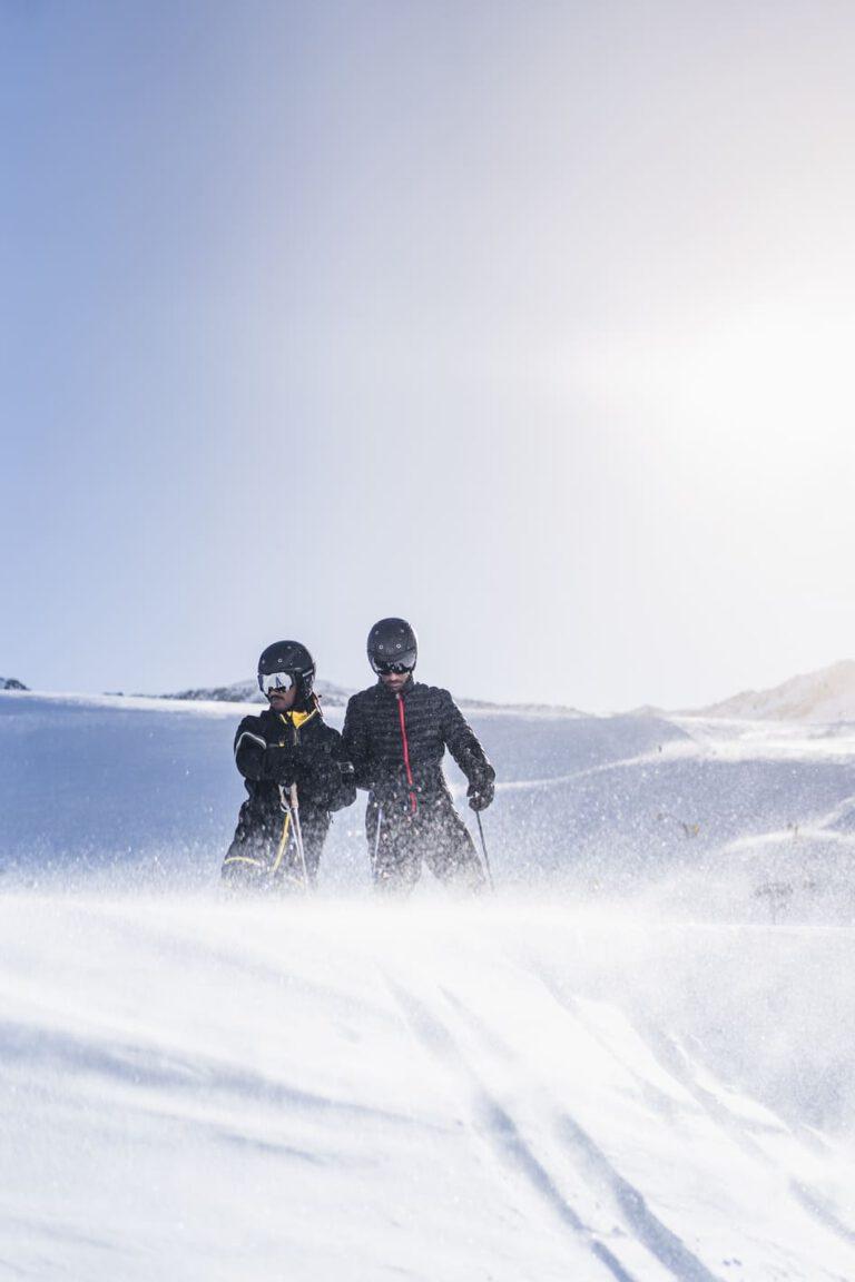Zwei Männer beim Skifahren auf einem Schneehügel - Chris Gollhofer Lifestylefotografie