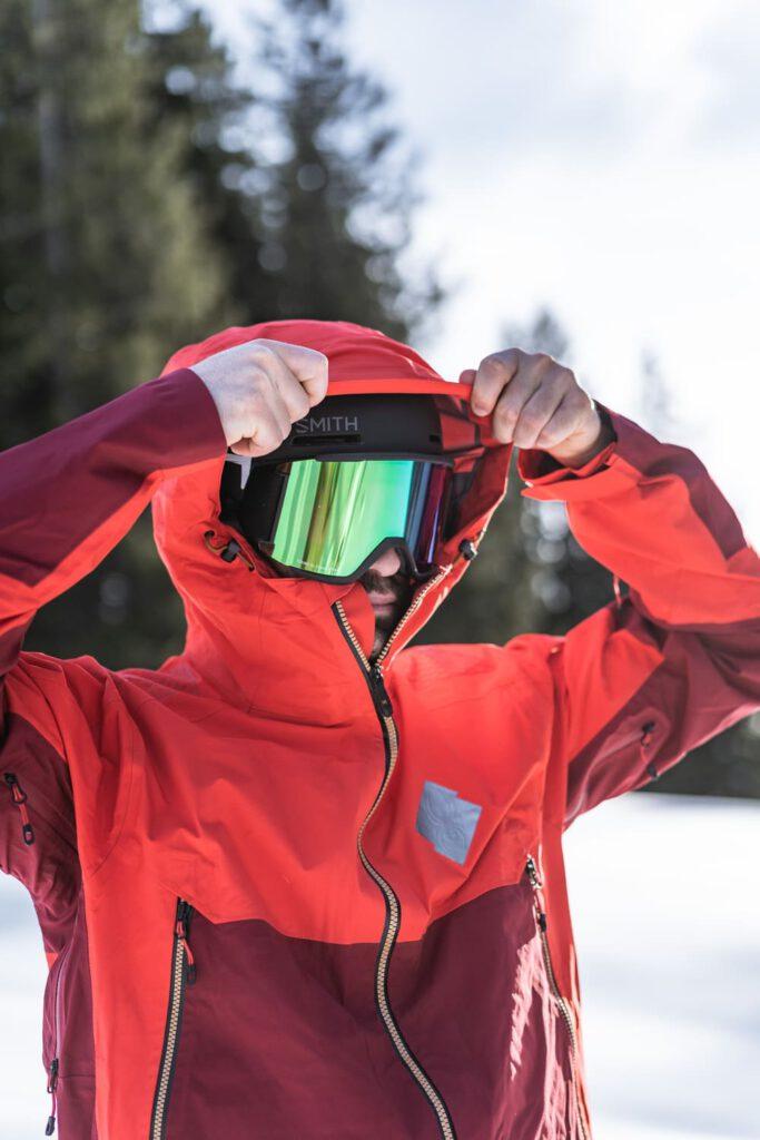 Mann zieht sich Kapuze über den Skihelm