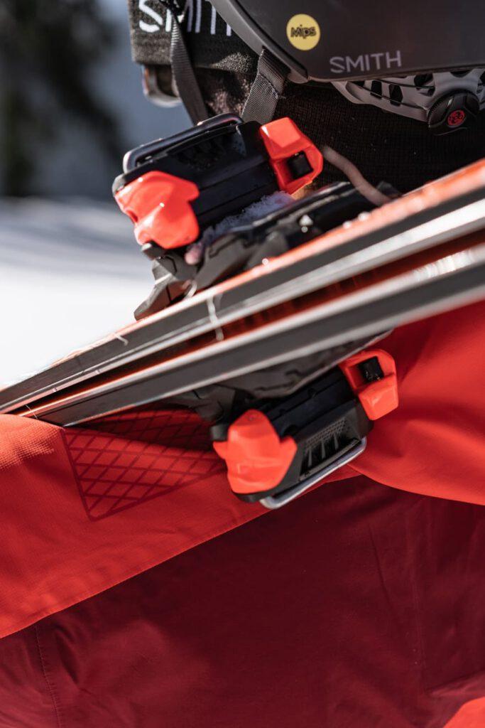 Person trägt Ski auf der Schulter