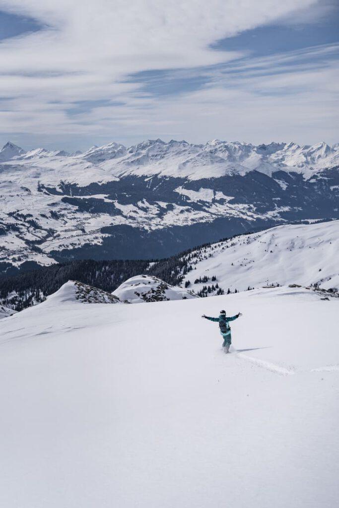 Eine Snowboarderin fährt alleine durch ein Tiefschneefeld