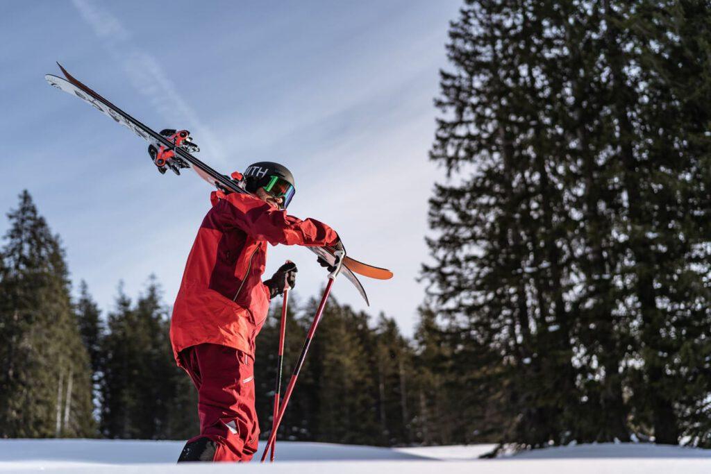 Mann läuft mit Ski auf der Schulter den Berg hinauf