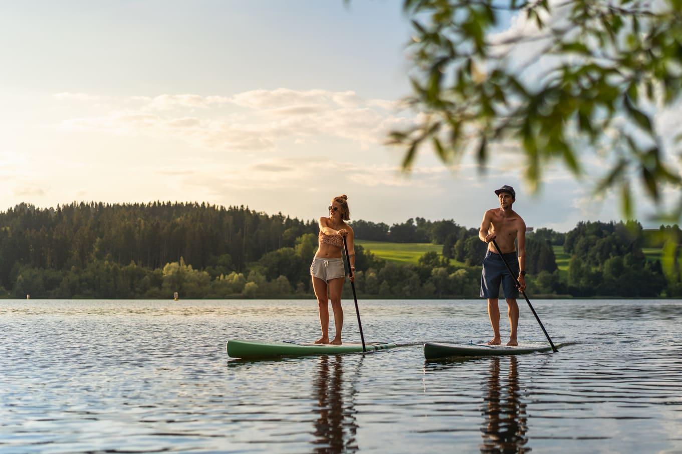 Ein Mann und eine Frau auf einem See beim stand up paddeln