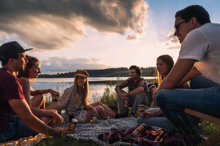 Eine Gruppe junger Menschen trinkt eiskalte Limonade beim Picknick an einem See