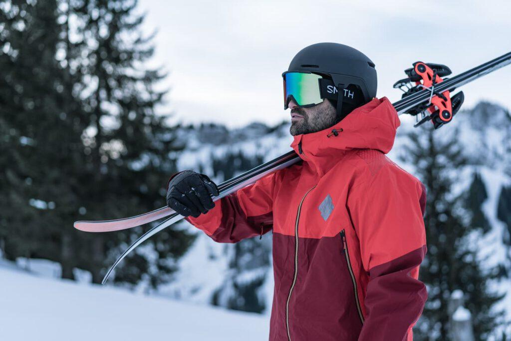 Mann trägt Ski auf seiner Schulter