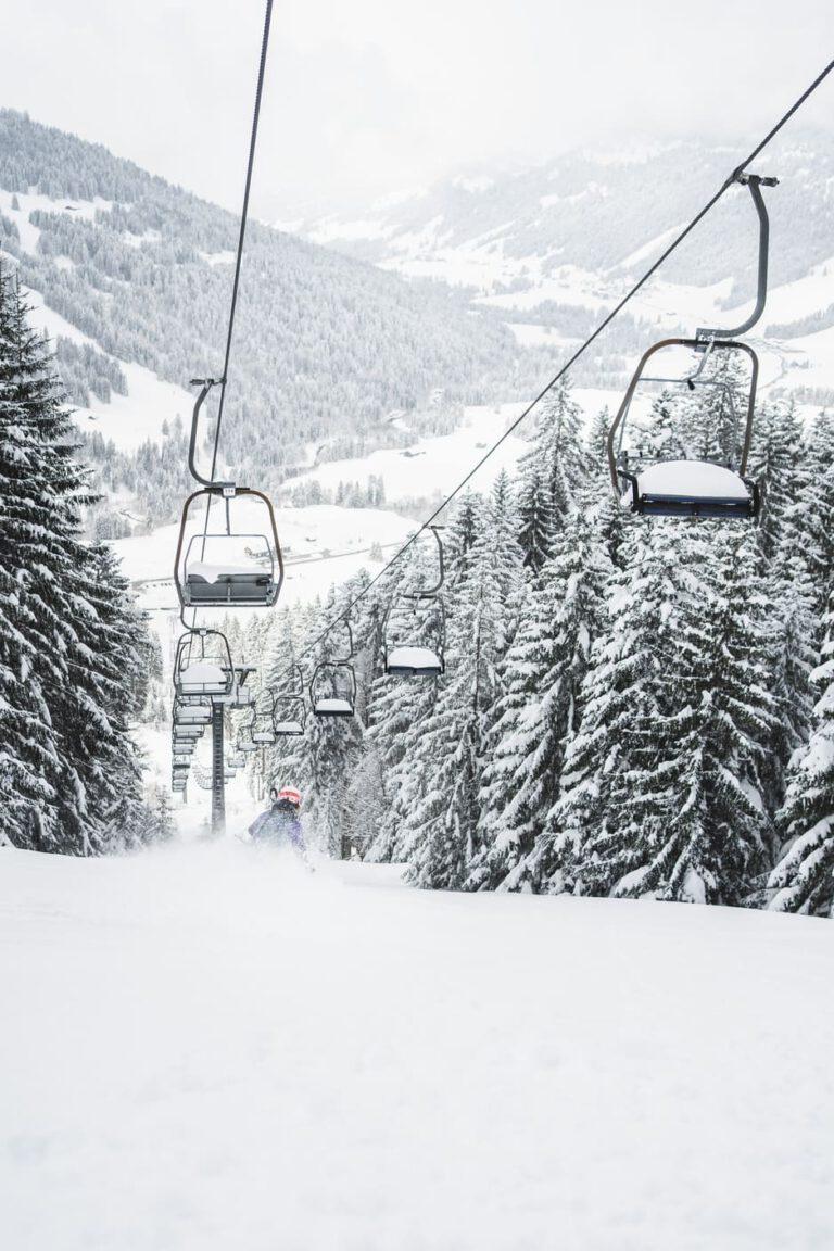 Frau fährt im tiefen Neuschnee unter einem Sessellift - Chris Gollhofer Sportfotografie Südtirol